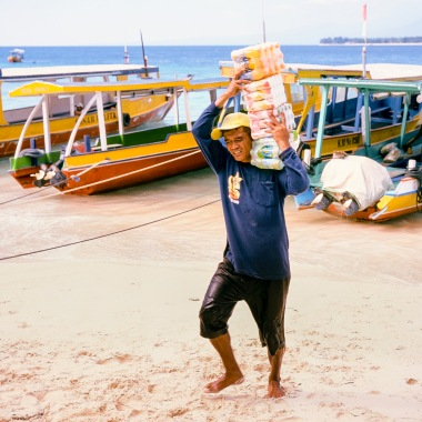 A porter is carrying goods ashore.