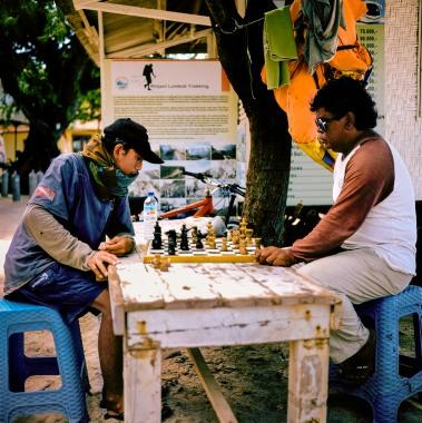 Tour guides playing chess on Gili Meno.