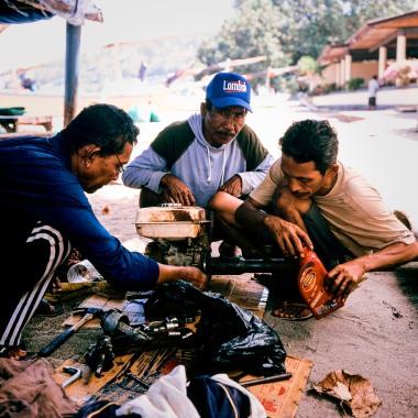 Gili Meno fishermen repairing a boat engine.